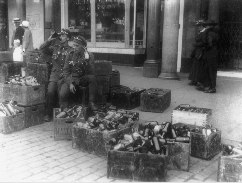 Soldiers sitting on beer crates at Armistice celebrations in the marketplace Courtesy of Nottingham City Council and www.picturethepast.org.uk